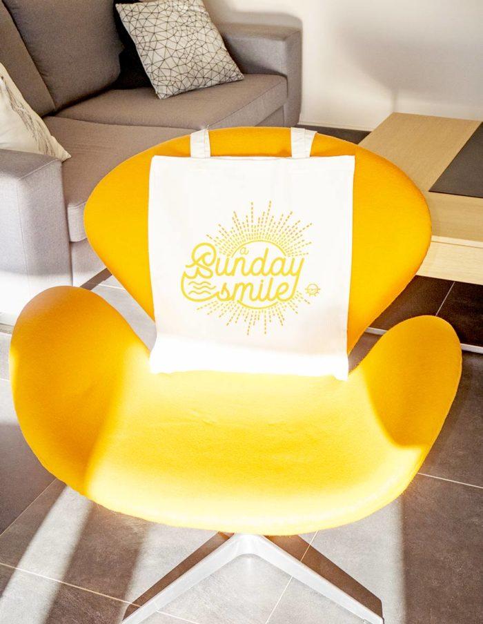 """Tote bag couleur naturelle écru, impression sur le devant """"A sunday Smile"""", posé sur fauteuil Swan"""
